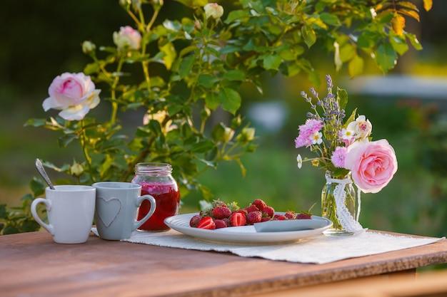 Чашки с розовыми розами на деревянном столе утром