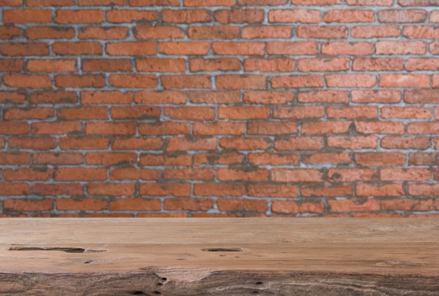 Teak wood table top with grunge brick wall blurred background