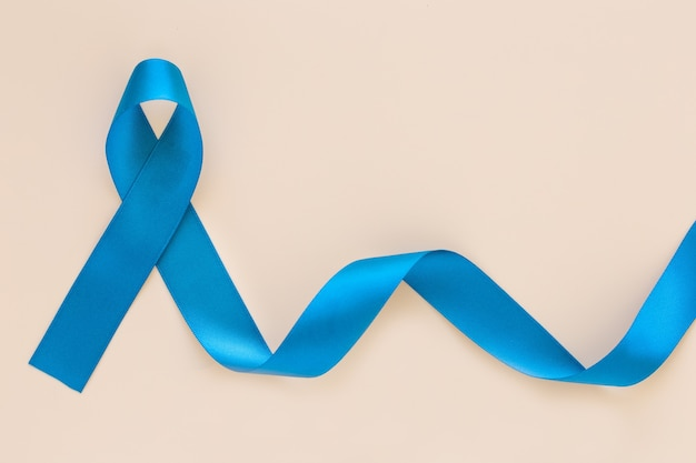 Teal color ribbon curl on white or beige isolated background, copy space.