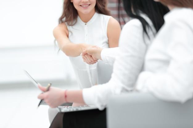 Команда и деловое рукопожатие двух женщин в офисе.