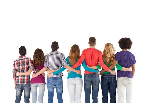 팀 빌딩. 흰색에 고립 된 동안 서로 가까이 서 있는 다민족 사람들의 후면 보기