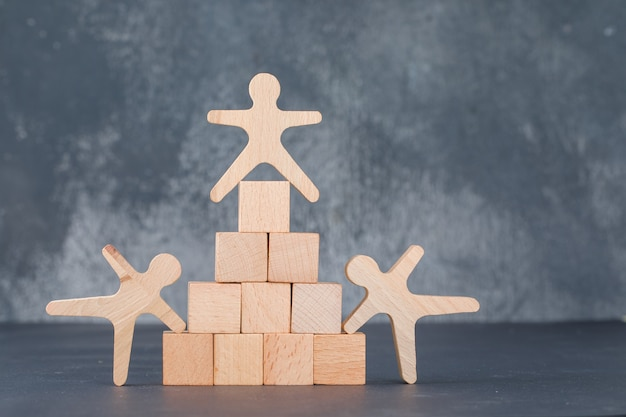 Team and business concept with wooden blocks like pyramid with wooden human figures.