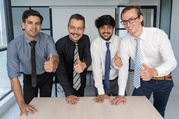 Team of business experts posing with thumbs up.