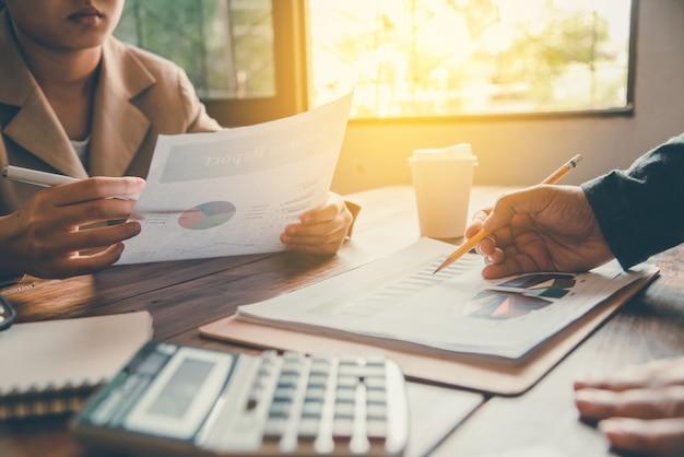 Командная работа делового человека. работая с документом для получения финансовой информации в офисе открытого пространства.