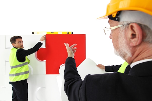 Team of business man and workers assmebling puzzle isolated on white