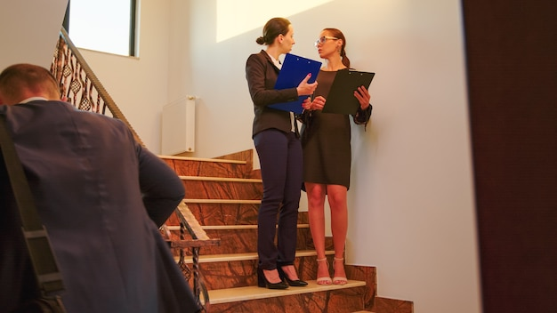 Team of business people and manager executive standing and walking on a staircase, talking holding clipboards. group of professional successful businesspeople working in modern financial building.