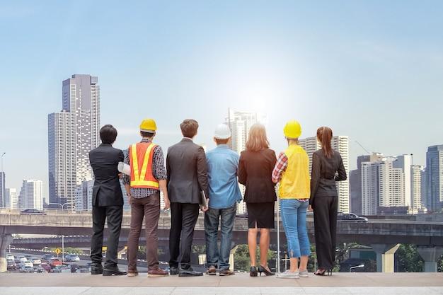 バンコクのバックグラウンドで交通渋滞とダウンタウンの超高層ビルに立っているエンジニアのプロのリアとチームのビジネスマン