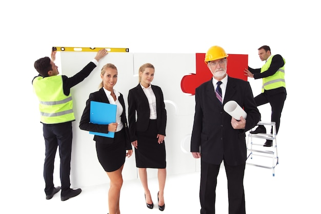 Team of business people and workers assmebling puzzle isolated on white