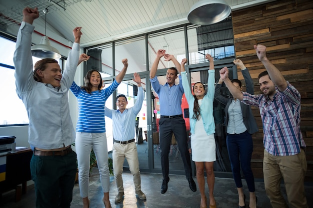 Team of businesspeople jumping in office