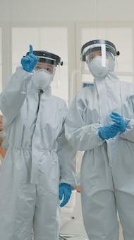 Team di dentisti caucasici con tute ignifughe che discutono di prevenzione