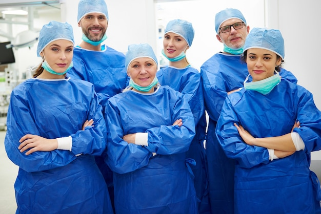Team of cheerful doctors in surgical uniform
