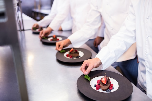 Team of chefs finishing dessert plates in the kitchen