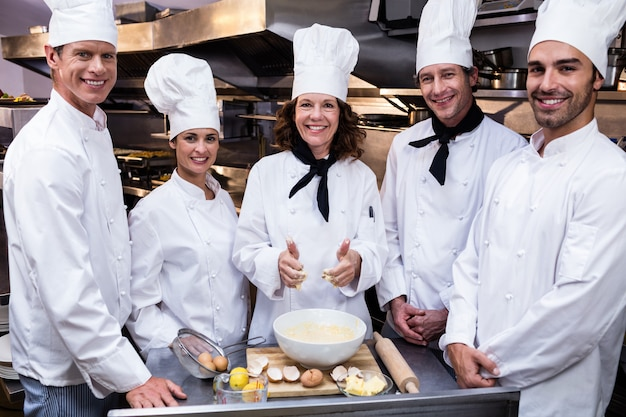 Team of chefs smiling in commercial kitchen