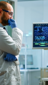 Team of chemists working with dna scan image looking at desktop standing in medical research laboratory, analysing biochemicals samples, talking. microbiology development with advanced equipment