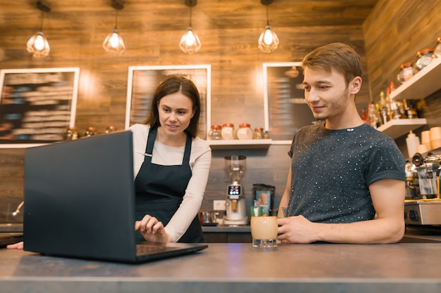 Team of coffee shop workers working near the counter with laptop