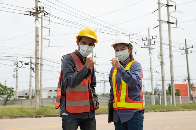 Team of electrical engineers inspects the quality of the installation of high voltage poles