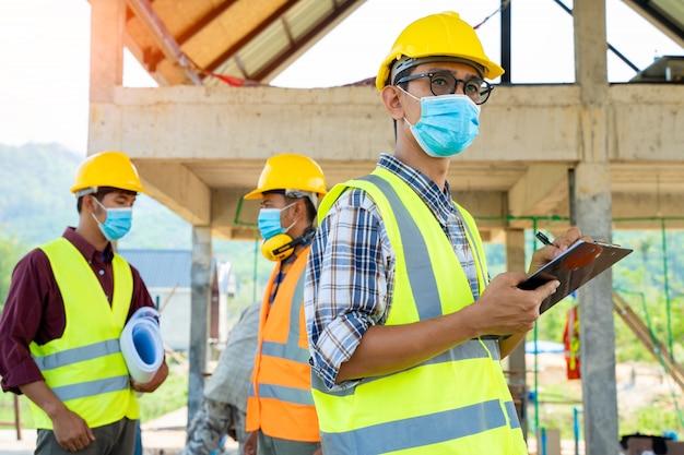 코로나 바이러스는 건설 현장에서 검사하는 동안 먼지와 막힘 병을 예방하기 위해 보호 마스크를 착용 한 팀 엔지니어와 빌더가 세계적인 비상 사태로 변했습니다.