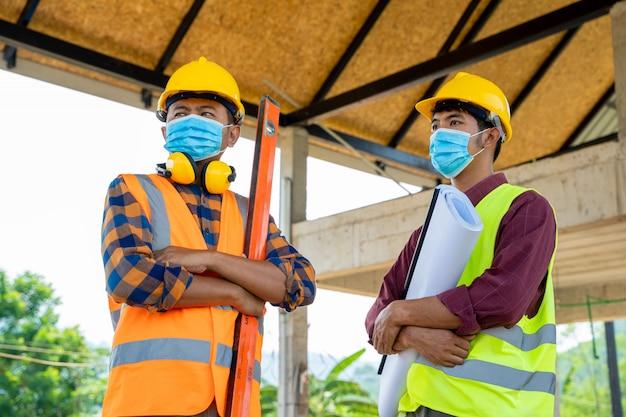 コロナウイルスは、建設現場での検査中に、ほこりやcovid 19の病気を防ぐために保護マスクを着用しているチームエンジニアとビルダーが、緊急事態になりました。