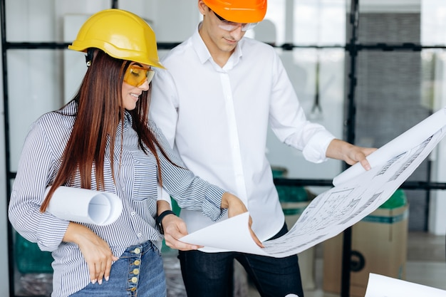 A team of engineers work in the office reviewing drawings
