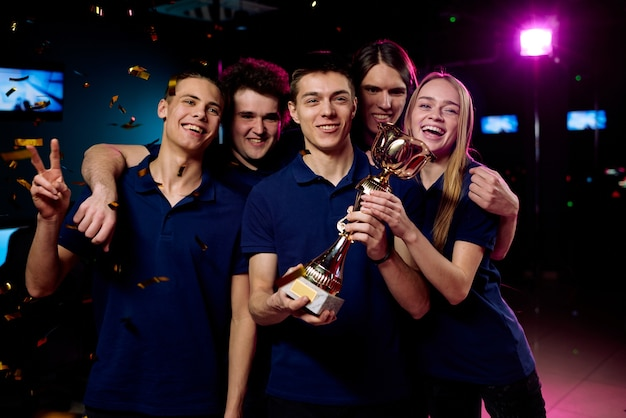 Team of excited teenage participants of e-sports video gaming competition showing prize for their victory