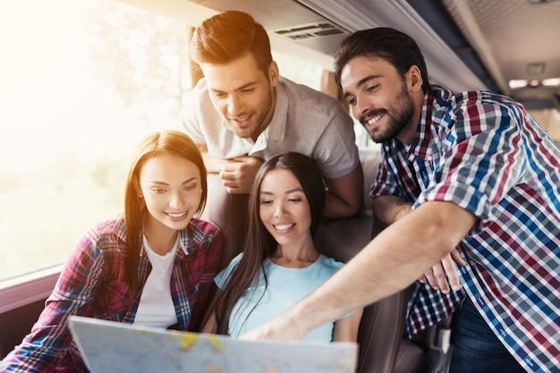 Команда возбужденной молодежи изучает карту в туристическом автобусе.