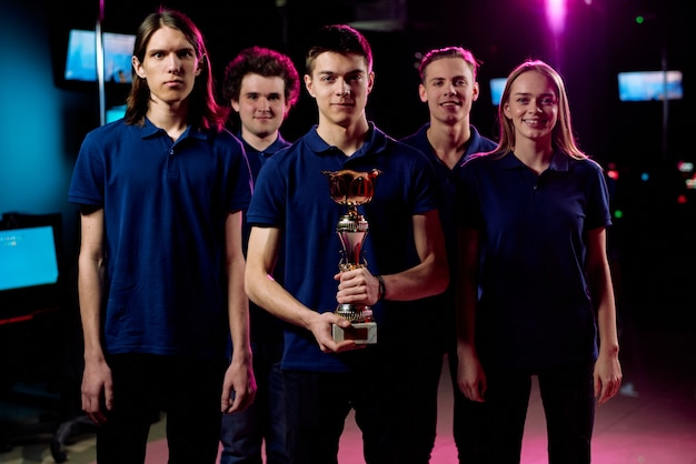 Team of five young champions in cybersports and network gaming competition standing in row in contemporary e-sports club