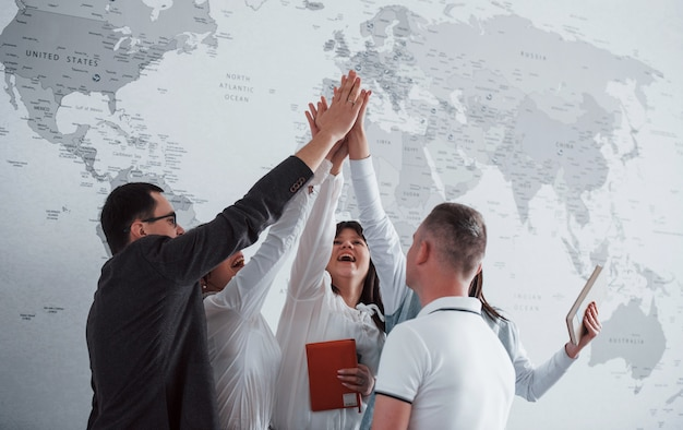 Team of freelancers standing against wall with map of the world on it