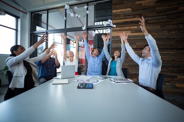 Team of graphic designers throwing paper ball up in air