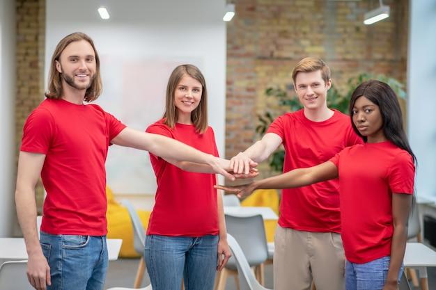 팀. 빨간 티셔츠와 청바지에 웃는 젊은 사람들의 그룹은 앞으로 함께 손을 뻗어 실내