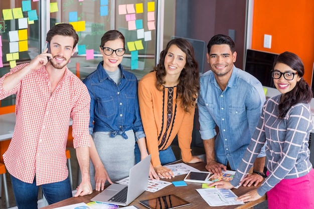 Team of happy graphic designers standing at table