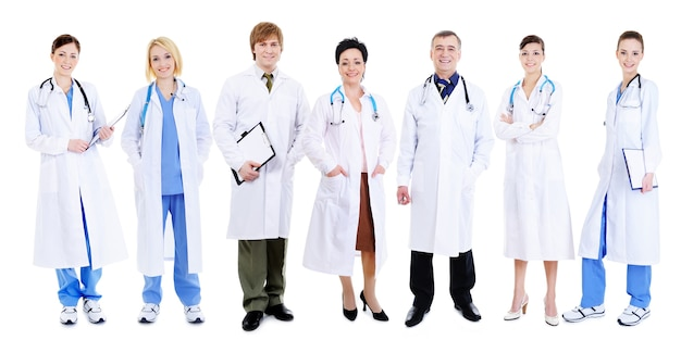 Team of happy laughing doctors standing in line on white