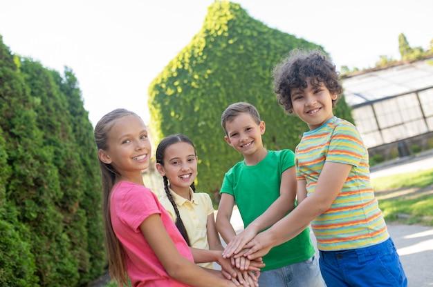 팀. 화창한 날에 녹색 공원에 원을 그리며 앞으로 팔을 뻗은 행복한 어린 소년 소녀들