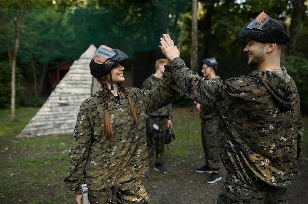 Команда в камуфляже и масках играет в пейнтбол, война на детской площадке в лесу. экстремальный спорт с пневматическим оружием и красящими пулями или маркерами, военная игра на открытом воздухе, тактика ведения боя