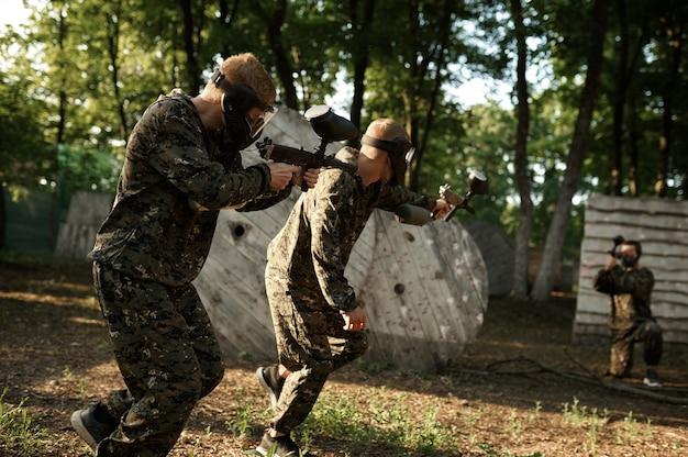 Команда в форме и масках играет в пейнтбол, сражается на детской площадке в лесу. экстремальный спорт с пневматическим оружием и красящими пулями или маркерами, военная игра на открытом воздухе, тактика ведения боя