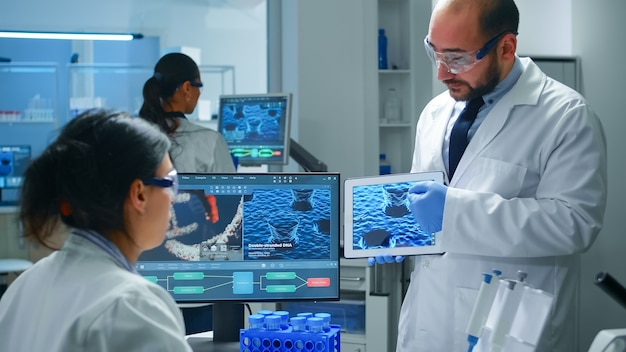 Team of industrial scientists, engineers, developers innovating new vaccine, doctor pointing on tablet explaining virus evolution to coworker
