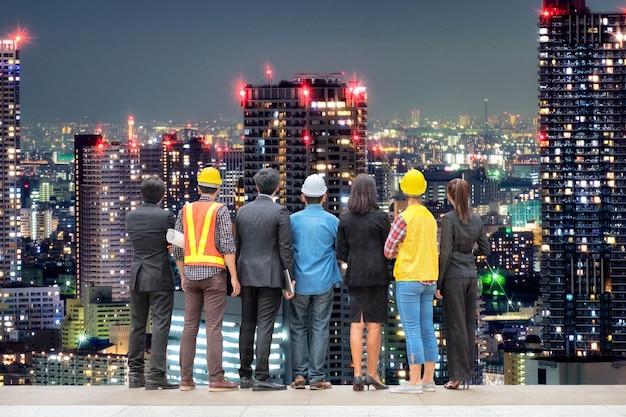 都市の背景の光の超高層ビルの塔に立っているエンジニアの専門家と国際的なビジネスの人々をチーム