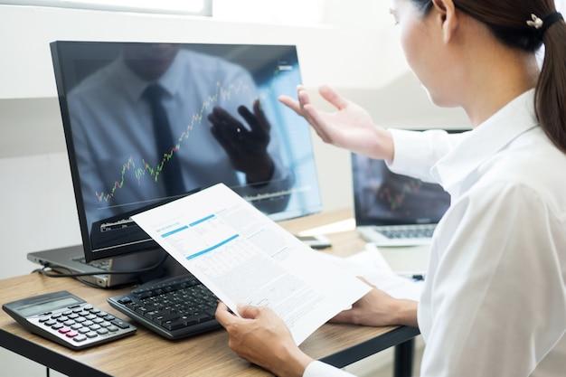 Team investment entrepreneur обсуждает и анализирует торговые графики и графики на компьютере