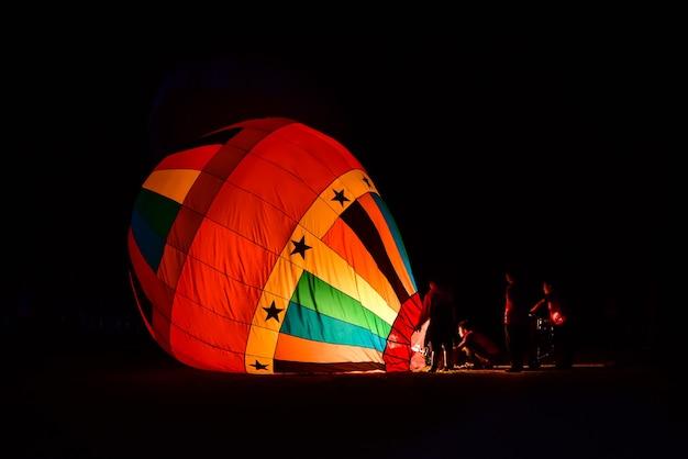 チームは気球を上昇させるために火で気球を準備しています。