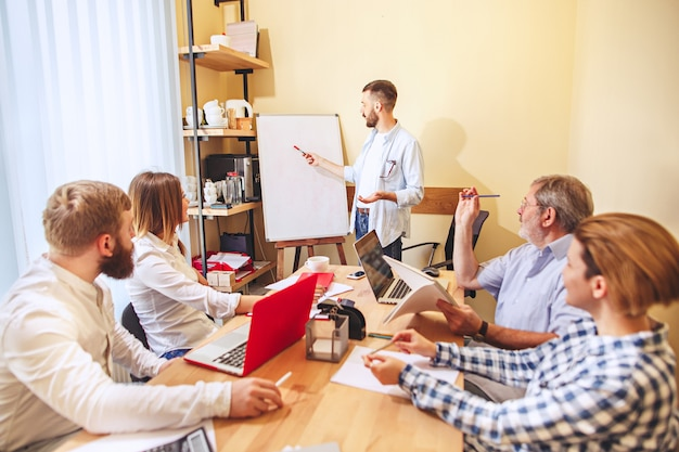 Командная работа. фото молодых бизнесменов, работающих с новым проектом в офисе