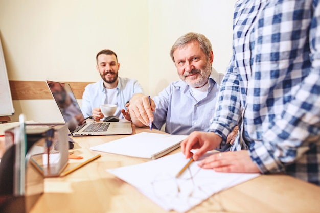 チームの仕事。オフィスで新しいプロジェクトを扱う若いビジネスマンの写真