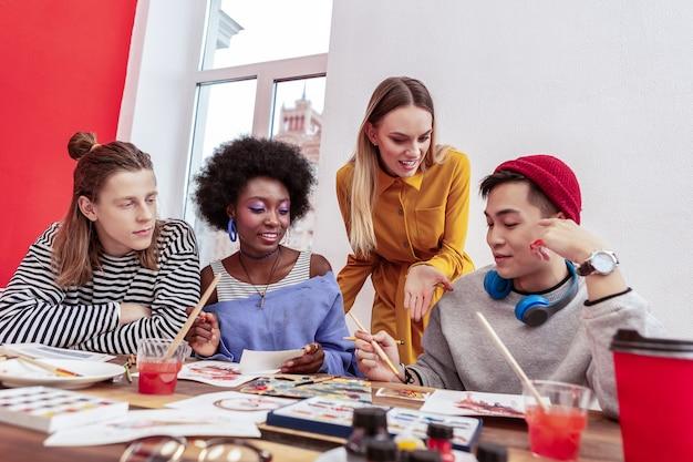 チームリーダー。仕事をしながら彼らと話している若いファッションデザイナーのブロンドの髪のチームリーダー