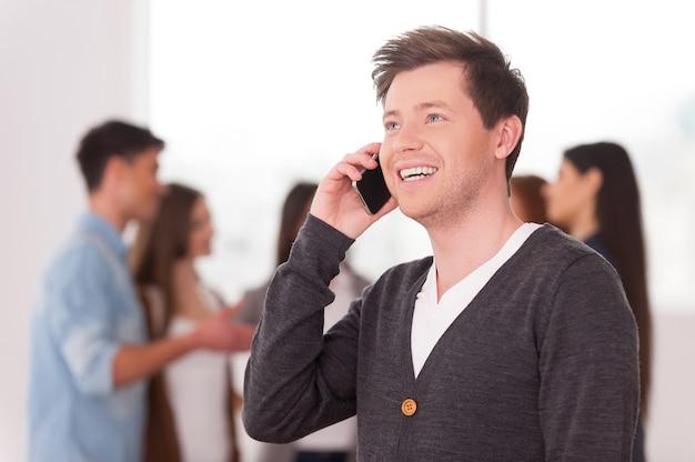 Руководитель группы по телефону. красивый молодой человек разговаривает по мобильному телефону и улыбается, пока группа людей общается на заднем плане