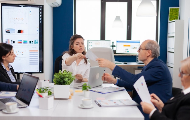 Team leader of start up giving tasks for multiethnic coworkers in company meeting room