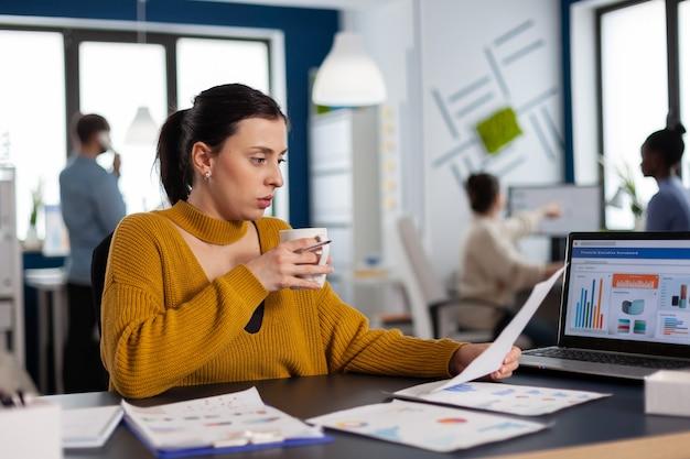 직장 마시는 커피에서 차트를 읽는 금융 회사의 팀 리더십. 다양한 동료들과 함께 프로젝트에 앉아 있는 임원 기업가, 관리자 리더.