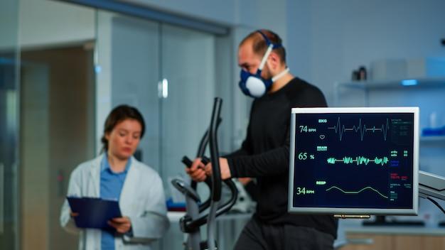 Team di ricercatori mediali che monitorano il vo2 degli sport da prestazione dell'uomo che indossano la maschera in esecuzione. medico di laboratorio che misura la resistenza dello sportivo mentre la scansione ekg viene eseguita sullo schermo del computer in laboratorio