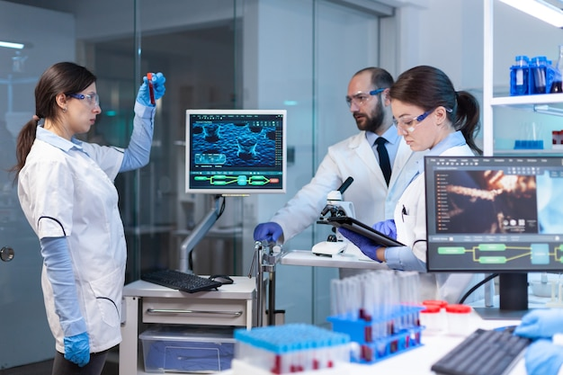Team of medical research scientists conducting vaccine development with help of high tech, test tubes, micropipette and writing down analysis results on computer in modern equipped laboratory at night