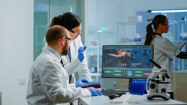 Team medical scientist conducting dna experiments looking in computer holding test tube with blood sample working in science laboratory. lab engineers in white coat analysing vaccine development