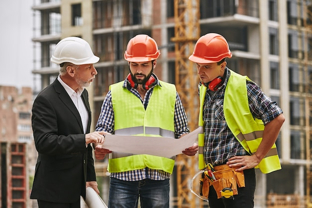두 명의 젊은 건축업자와 함께 정장을 입고 흰색 헬멧을 쓴 팀 회의 메인 엔지니어는