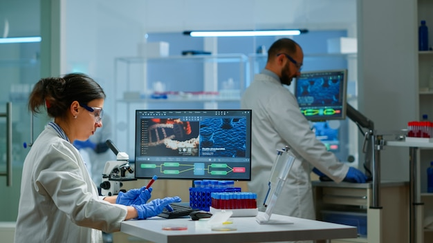 Team of microbiology scientists discussing about virus development in modern equpped laboratory using computer analysing test blood samples and develop vaccine, drugs and antibiotics against covid-19.