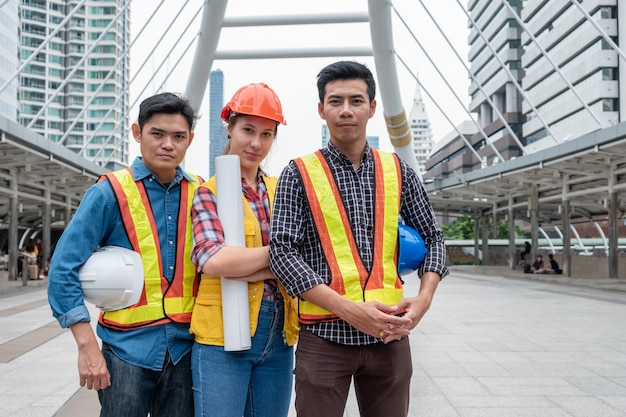 Team of multi ethnic engineer confidence standing and holding blueprint, safety helmet in construction site at urban